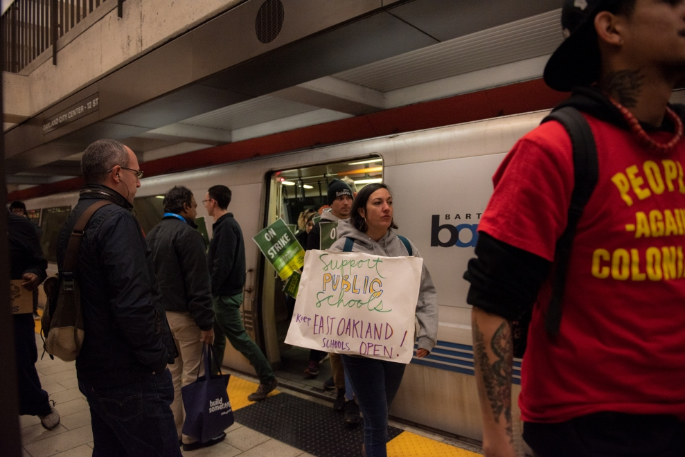 Teachers from Roots Academy in Oakland, Calif., hold signs as they exit the subway downtown.