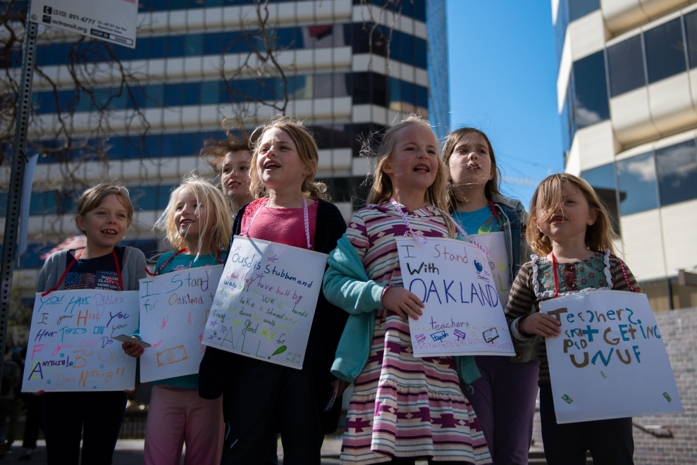 """Holding homemade signs, young students from Glenview Elementary School chanted as the march passed by: """"Get up! Get down! Oakland is a union town!"""""""