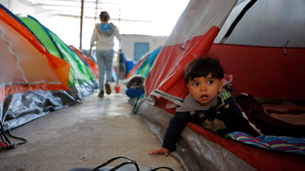 A 10-month-old looks out from his family's tent in a shelter for migrants in Tijuana, Mexico.