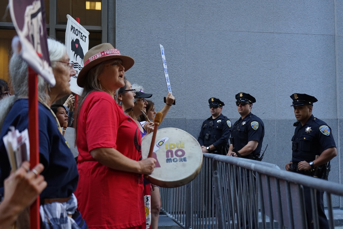 Pennie Opal Plant of Idle No More SF Bay leads songs and prayer outside of Wells Fargo.