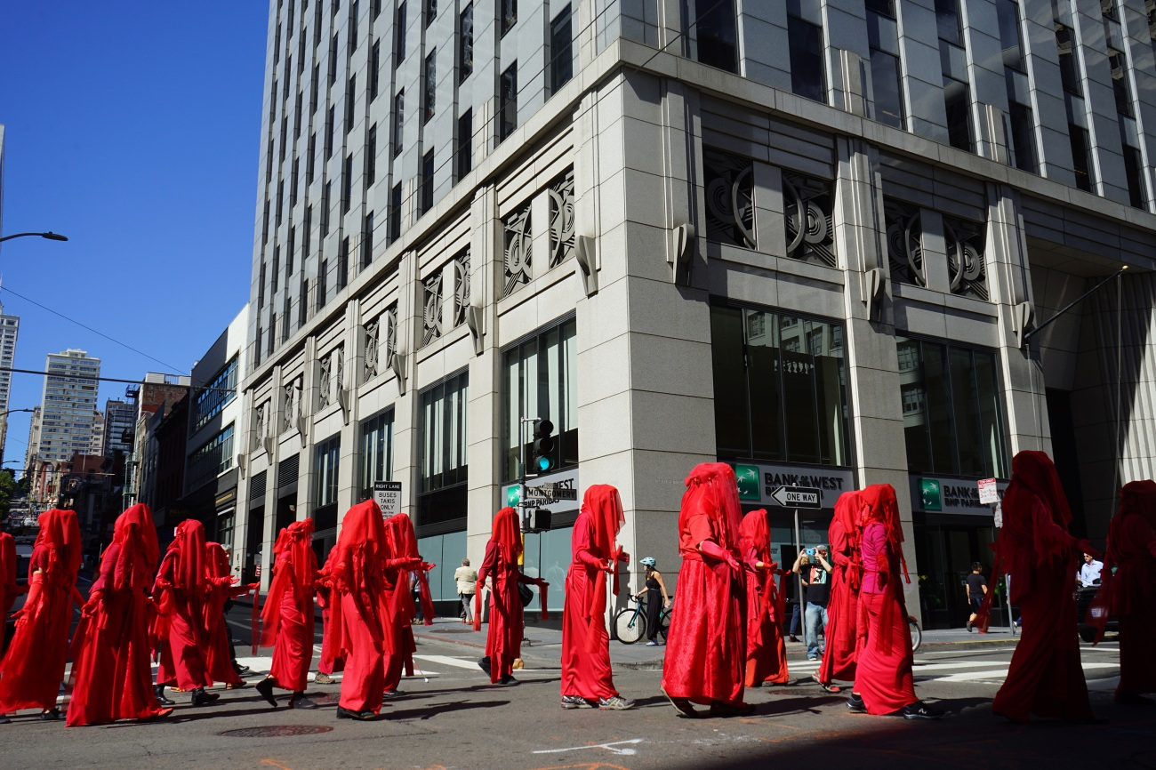 "Calling themselves ""the Red Rebels,"" a flock of demonstrators in canary red robes moved dramatically slowly through the streets."
