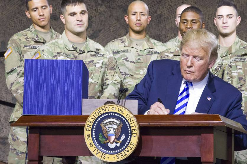President Trump signs a bill at a small desk, with six US Army men behind him.