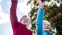 Elizabeth Warren and Hillary Clinton waving