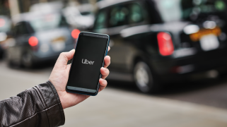 A hand in a black leather jacket uses the Uber app on a smartphone with a black London taxi in the background.