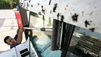 A man wipes bug splatters off the windshield of his large van; there are even more splatters above the windshield.
