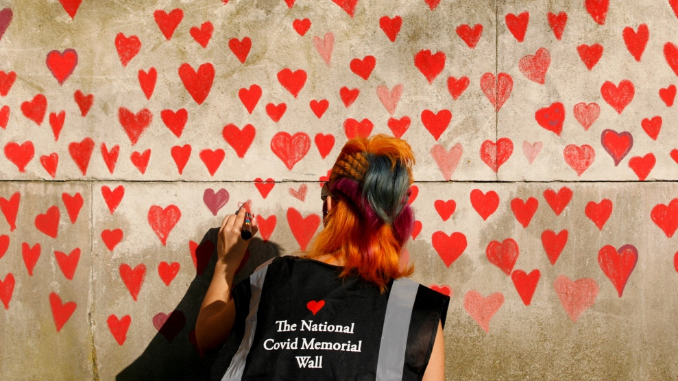 A woman draws red hearts representing individual coronavirus deaths onto the newly-unveiled National Covid Memorial Wall opposite the Houses of Parliament in London, England, on March 30, 2021.