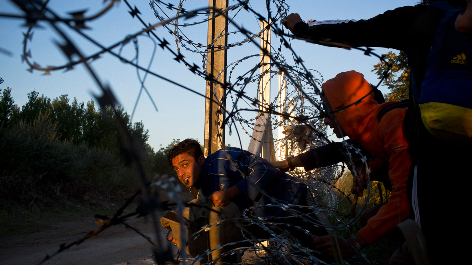 Refugees crossing through barbed wire fence.