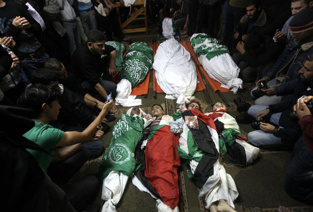 Nov. 19, 2012 - Gaza City, Gaza Strip - Palestinian mourners gather around the bodies of the al-Dallu family during their funeral in Gaza City.  © Majdi Fathi